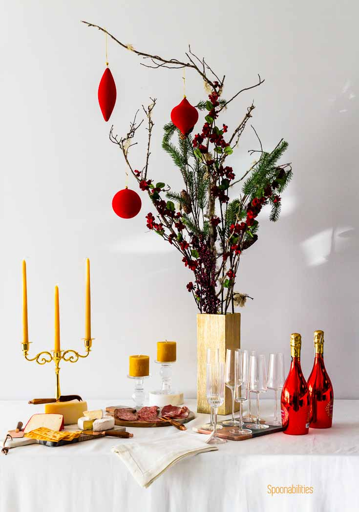 Holiday table decorated with Pillar Candles, drinks, food & flowers in a table with white tablecloth. Spoonabilities.com