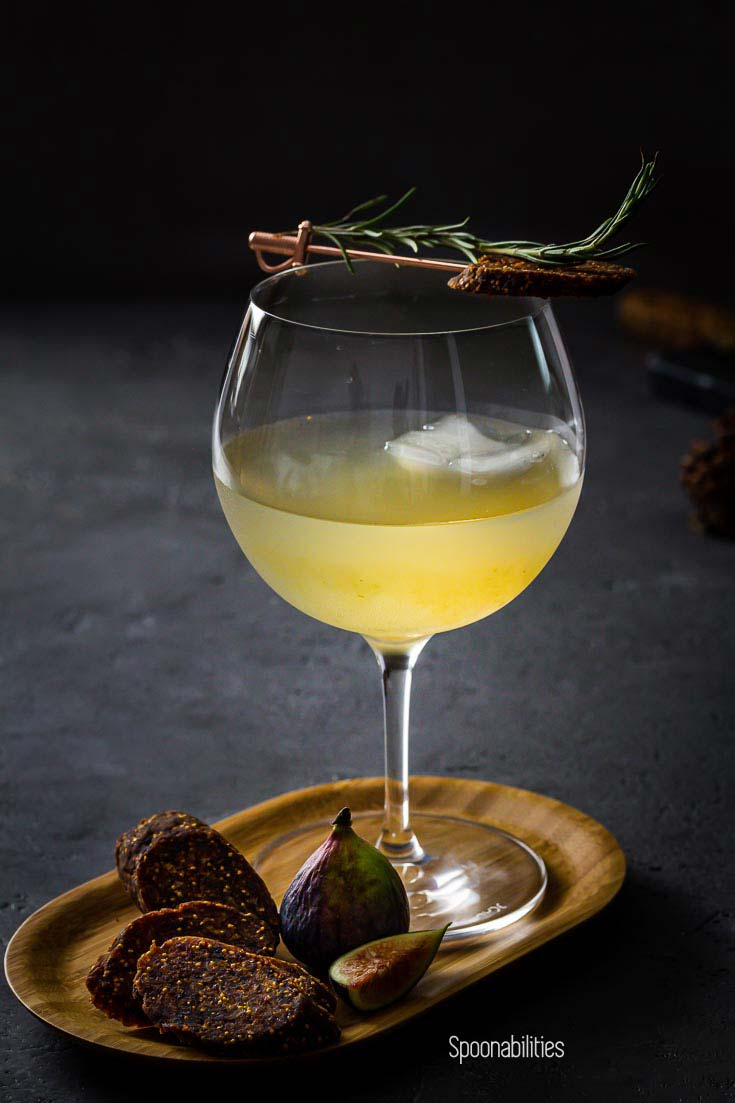 Closeup photo of Bloomsbury Garden Cocktail with large ice cube, and rosemary and fig salami garnish