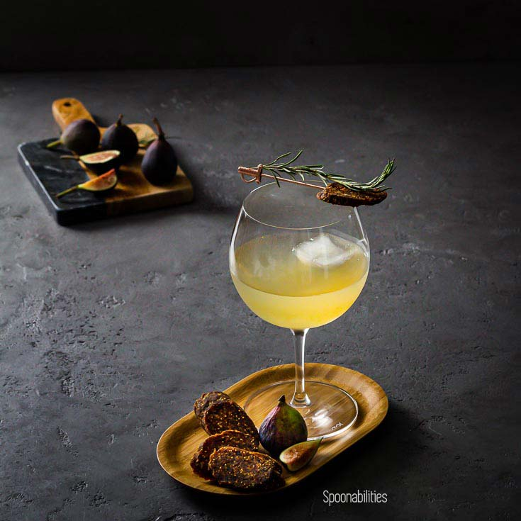 Glass of Rosemary Gin, Elderflower & Fig Tonic on a small wood tray with figs