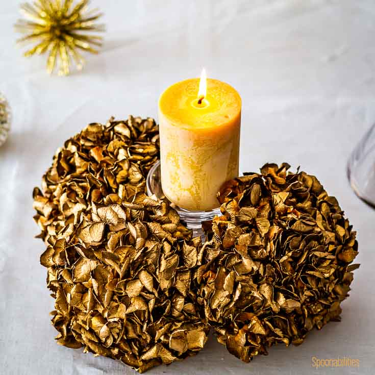 A pillar candle in a base with golden flowers on a table in a white tablecloth. Spoonabilities.com