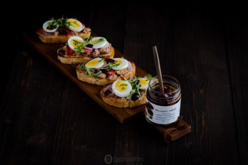 Wooden narrow serving board with Tuna Nicoise Toast and in front a open jar of Anise Marinated Kalamata Olives. Available at Spoonabilities.com