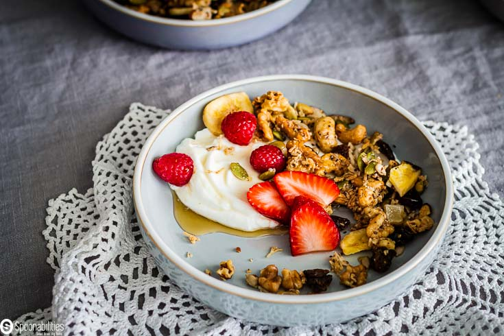 Light blue bowl with Greek yogurt, grain-free granola with strawberries and raspberry with a drizzle of maple syrup. Recipe at Spoonabilities.com