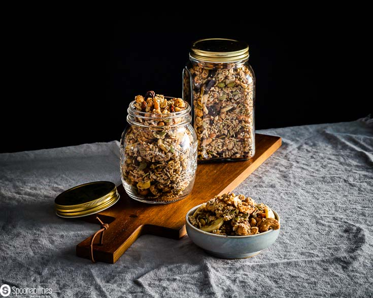 Granola packed in two glass jars on top of a wooden board and next to the front jar, there is a small bowl with some granola. Available at Spoonabilities.com