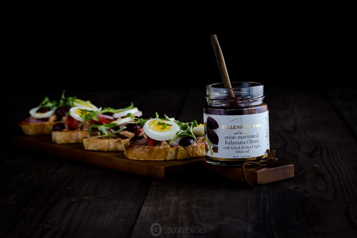 A jar of Anise Marinated Kalamata Olives with Greek extra virgin olive oil. In the background four Nicoise Toast with Tuna. Available at Spoonabilities.com