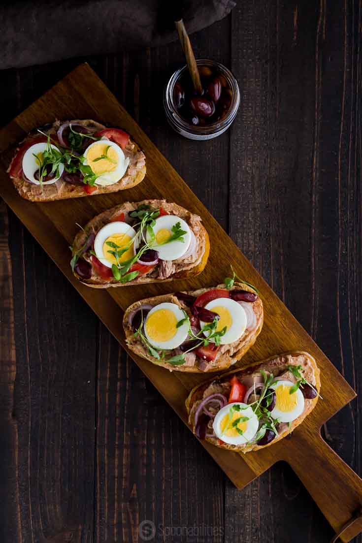 Overhead photo with a wooden serving board with four tuna toast with eggs, tomato and kalamata olives. Available at Spoonabilities.com