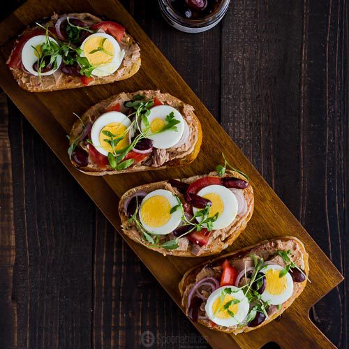 Square photo with an overhead shoot for the Tuna Nicoise Crostini using Anise Marinated Kalamata Olives. Available at Spoonabilities.com
