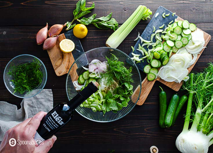 The slaw ingredients in a glass bowl and adding the Eleia extra virgin olive oil. Recipe at Spoonabilities.com