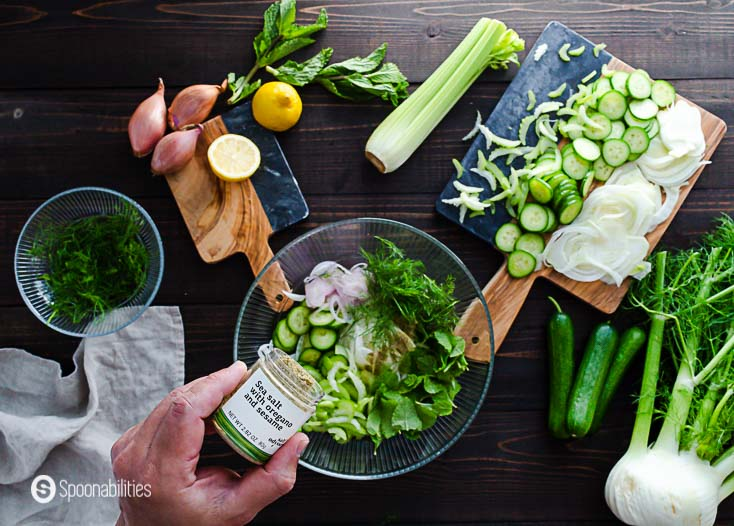 The slaw ingredients in a glass bowl and adding the sea salt with oregano and sesame. Recipe at Spoonabilities.com