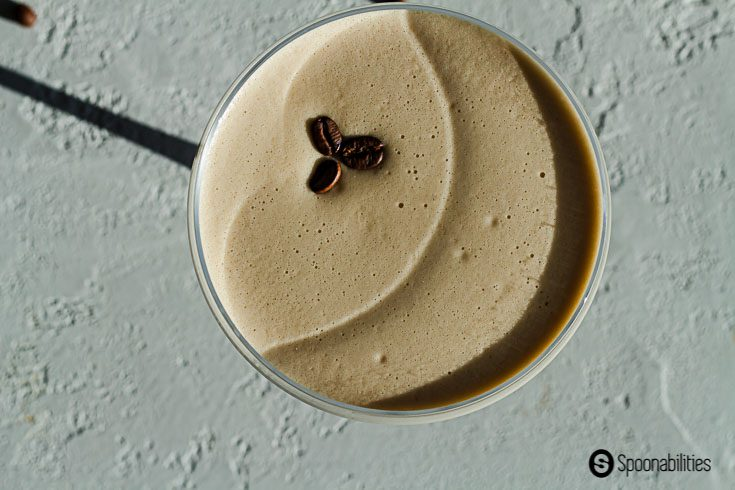 Overhead closeup of 3 coffee beans sitting on a bed of foam in an Espresso Martini