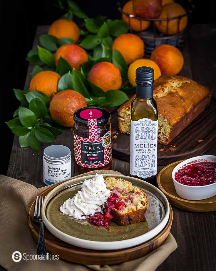 Blood Orange olive oil cake in the front of the photo on a plate. In the background Melies extra olive oil, Trea Wildflower honey & Greek Sea Salt. More gourmet products at Spoonabilities.com