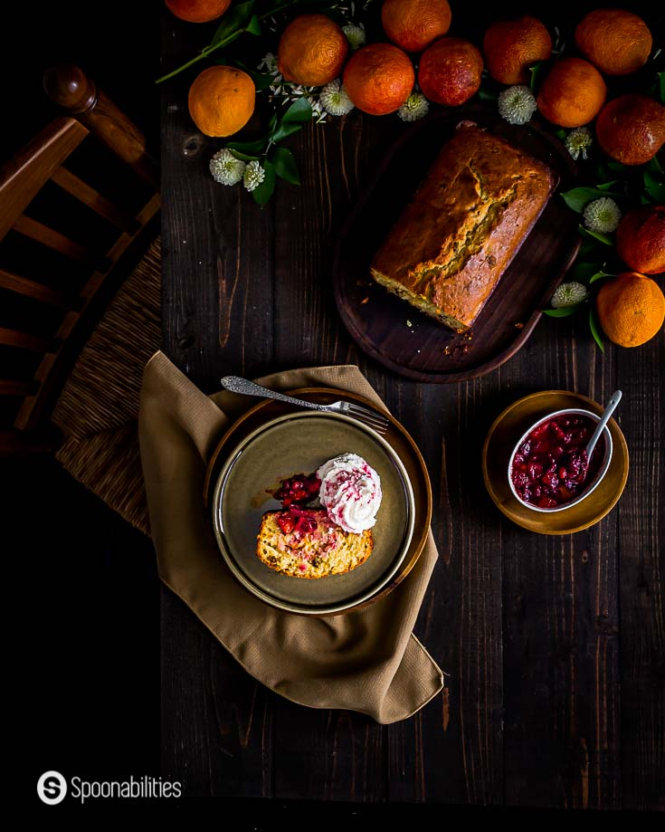 Blood orange cake served with blood orange compote in a dark wooden table with a beautiful set up with fresh fruits. More details at Spoonabilities.com