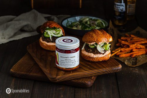 A jar of Sweet Red Pepper & Graviera Cheese Spread. In the background two spiced lamb burger with sweet potatoes fries on the side. Spoonabilities.com