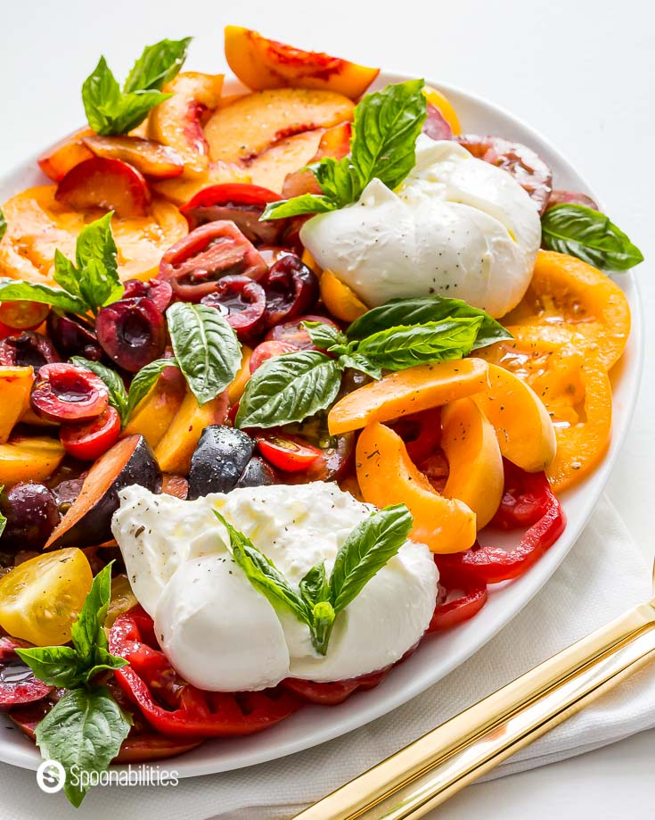 Photo of the caprese salad with stone fruits on a white oval plate with golden serving ware. Recipe at Spoonabilities.com