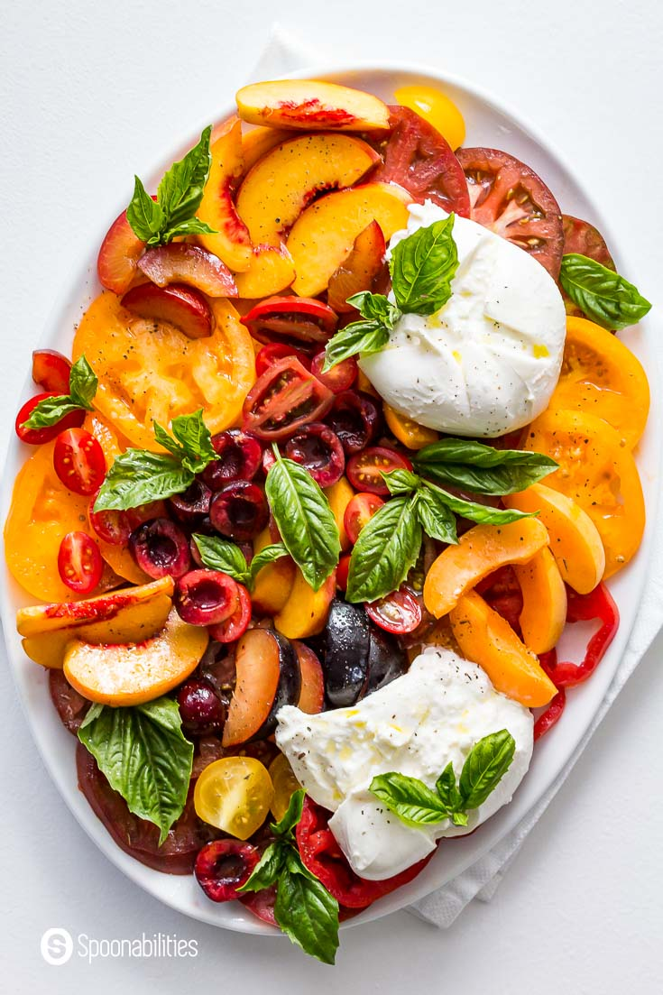 Overhead photo of the Stone Fruit Caprese salad presented in a oval white serving plate. Recipe at Spoonabilities.com