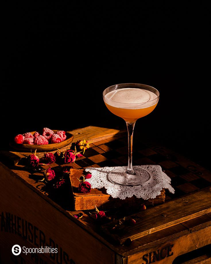 French martini on a white doily with frosted fresh raspberries