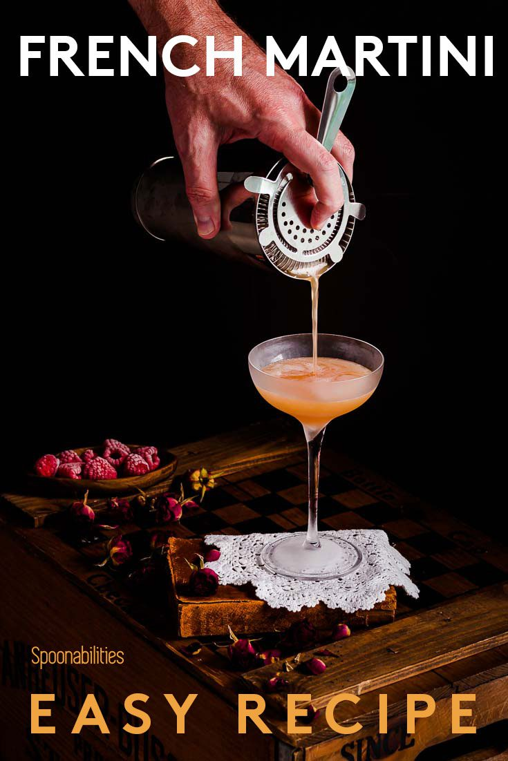 Hand straining a French Martini into a chilled martini glass