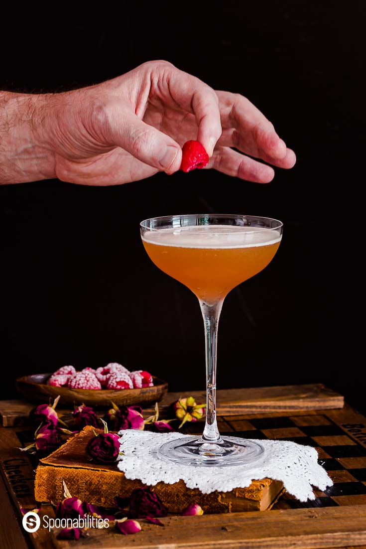 hand placing a fresh raspberry as a garnish on top of a french martini