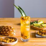 A tall glass in the center of the photo with a Grilled Pineapple Mojito. Around the glass pieces of pineapple and cutting board. Recipe at Spoonabilities.com