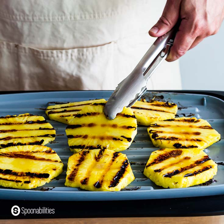 Grilling eight pineapple rings in a electric grill. Recipe at Spoonabilities.com