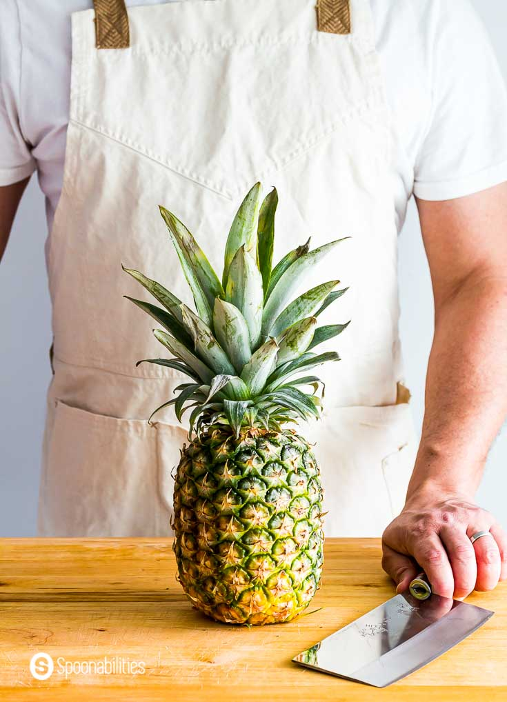 One pineapple on top of the counter top. Behind the pineapple is a guys with a knife, ready to cut the fruit. Recipe at spoonabilities.com
