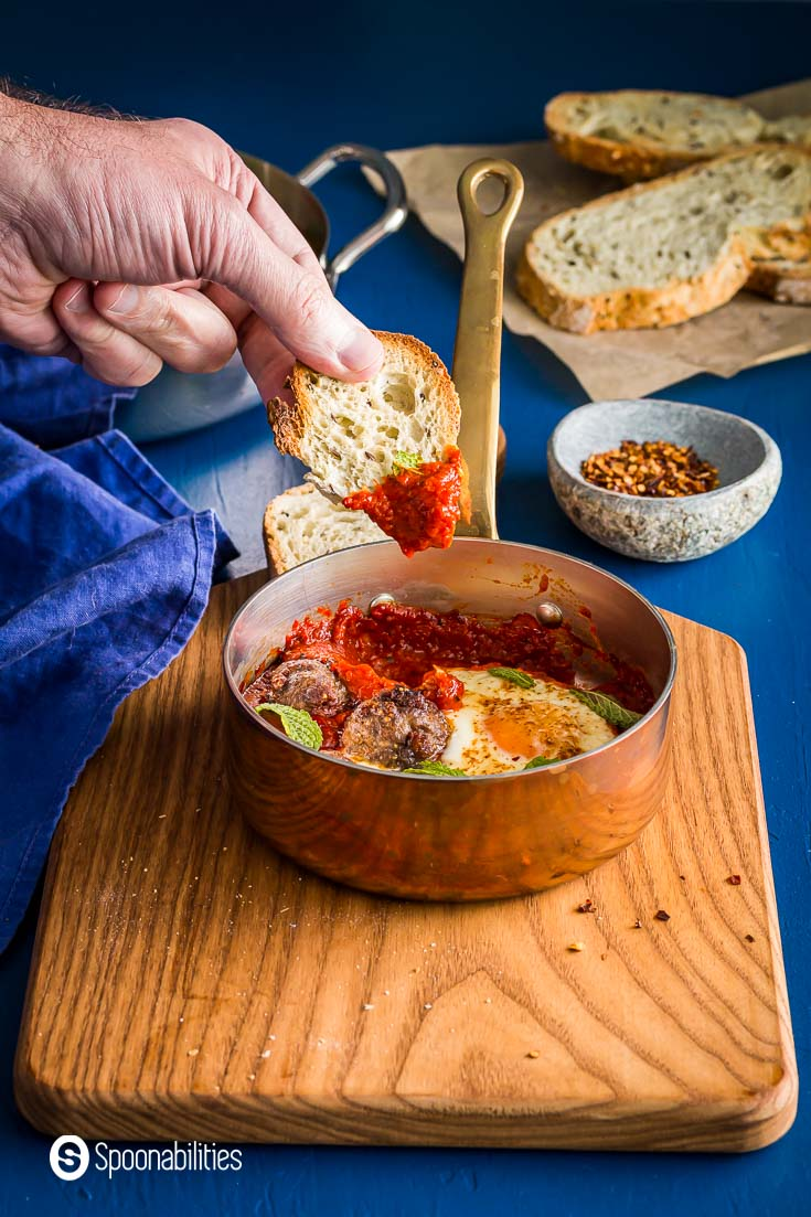 Soaking a piece of crusty bread into the roasted red pepper and tomato sauce from the shakshuka. Spoonabilities.com