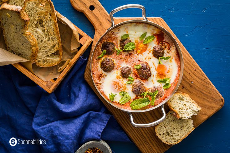 Blue background with a small saucepan with eight lamb meatballs in a tomato & red pepper sauce with three poached eggs. Served with 3 crusty bread in a wooden basket and smoked chili flakes in a small stone bowl. Recipe at Spoonabilities.com