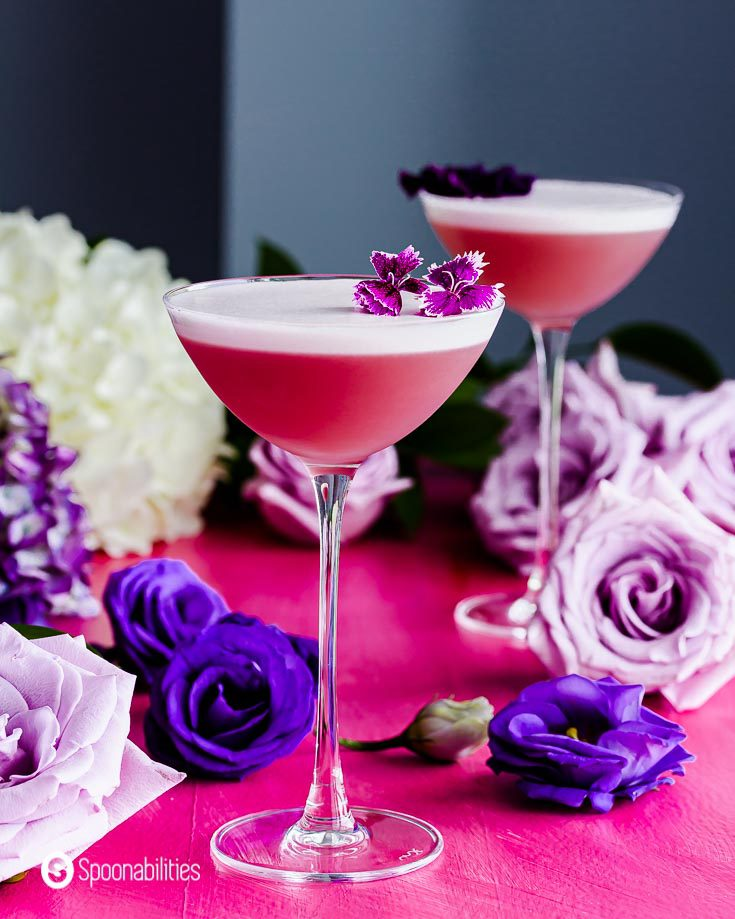 Close up of a cocktail glass with the Gin Violette Cocktail in the center. In the background roses in different purple tones. Recipe at Spoonabilities.com