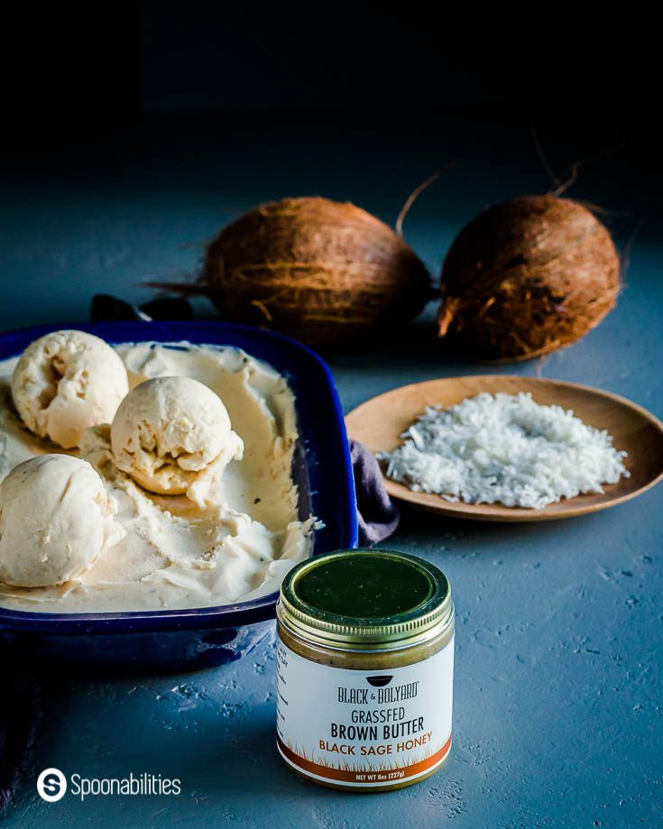 A Jar of Black Sage Honey Brown Butter in front of a blue container with ice cream. Also, on the right side a plate with coconut flakes and in the back two coconuts. Recipe at Spoonabilities.com
