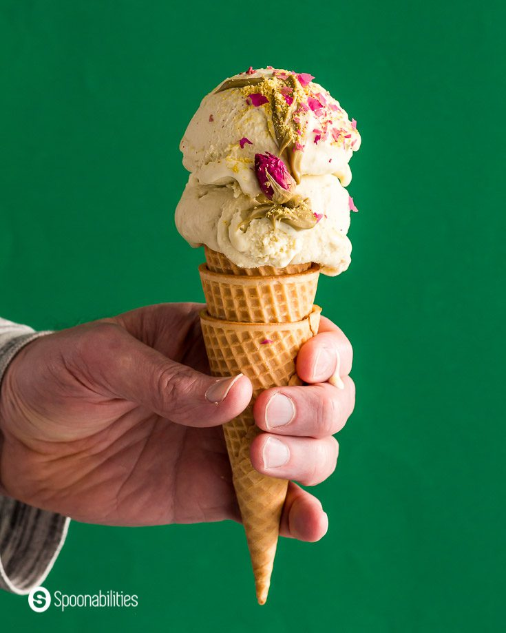 A hand holding a sugar cone with two scoops of Pistachio Ice cream with Rosewater & Saffron. Recipe at Spoonabilities.com