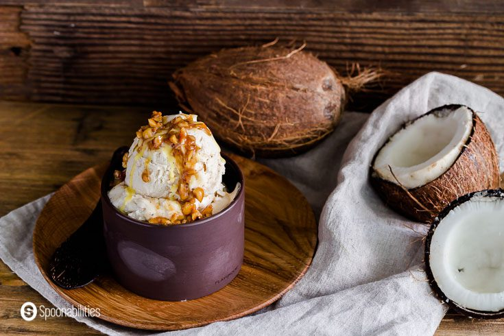 Photo in a rustic/tropical set up with a dark brown bowl on top of a wooden plate with two scoops of ice cream. In the background one whole coconut and another open showing the coconut meat. Recipe at spoonabilities.com