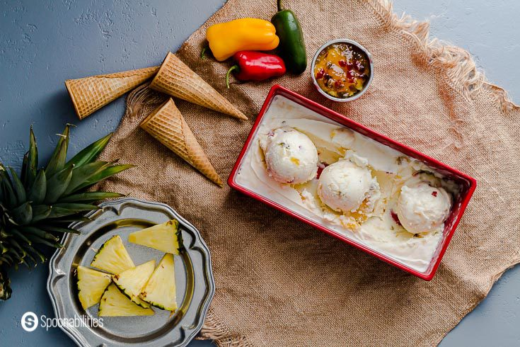 photo with a Tropical decor. In the center a red ice cream container with Paradise Pineapple Jalapeno Ice Cream with three scoop and around you will see pineapple triangles, peppers and sugar cones. Spoonabilities.com