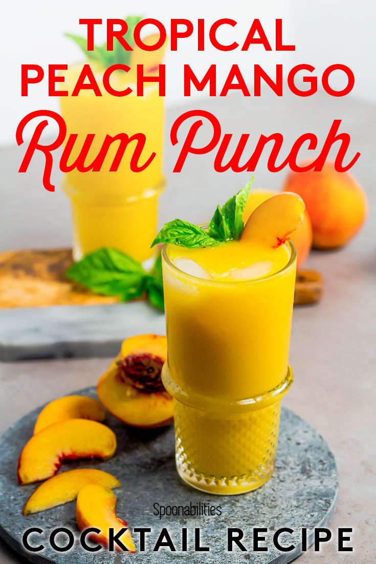 Pinterest photo with the Tropical Peach Mango Rum Punch on top of a marble round tray. Next to the glass is a half a peach with 4 slices. Recipe at Spoonabilities.com