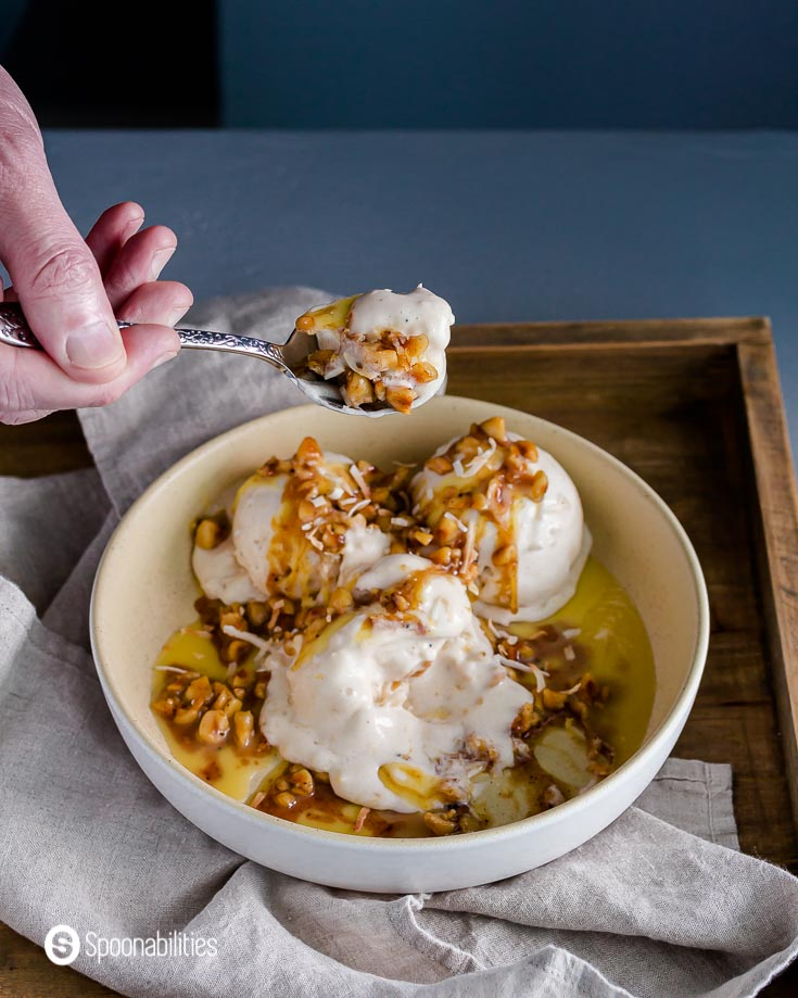 A bowl with the ice cream and the Hazelnut Brown Butter Sage Sauce. A hand spooning out some of the ice cream. Recipe at Spoonabilities.com