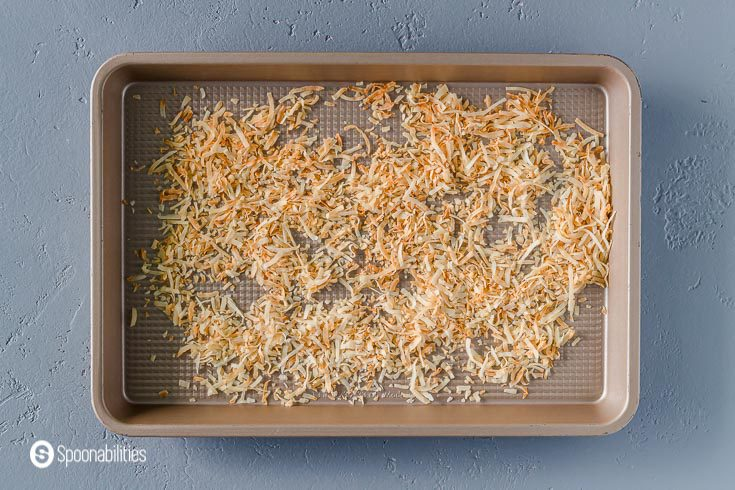 Toasted coconut flakes in a small baking tray. Recipe at Spoonabilities.com