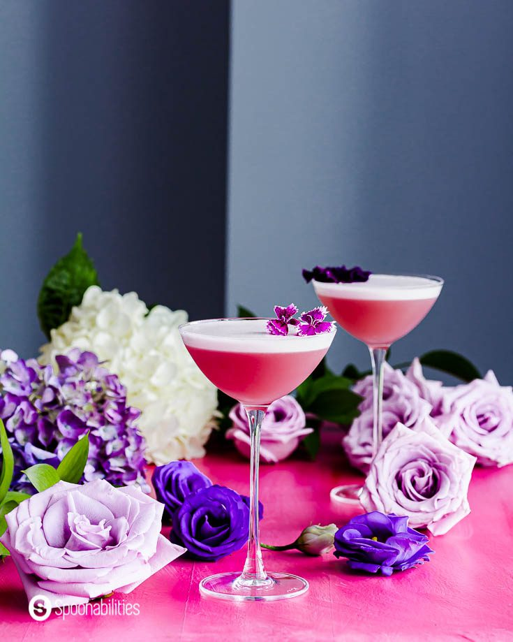 Two cocktail glasses on top of a pink surface with different tones of purple roses around the scene. The two glasses have the Gin Violette Cocktail with a beautiful froth and garnished with edible flowers. Recipe at Spoonabilities.com