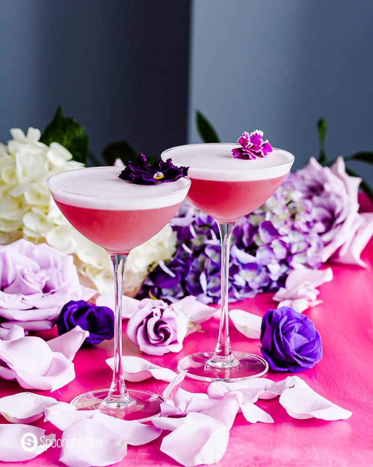 Two beautiful cocktails in a elegant glassware from the new NUDE Savage coupetini glasses. The surface is decorated with rose petals and the background has white and purple hydrangeas. Recipe at Spoonabilities.com