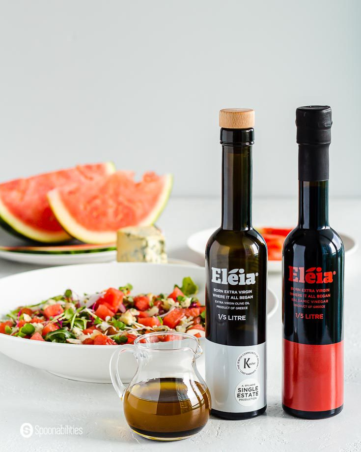 In the background a summer salad and in the front two black bottle and next to them a small glass container with a balsamic vinaigrette. The bottles are Eleia extra virgin olive oil and balsamic vinegar. Products available at Spoonabilities.com