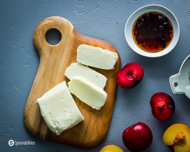 Cutting board with Halloumi cheese, plums and Cherry Ancho Chili Sauce. Recipe at Spoonabilities.com