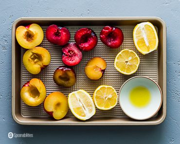 Baking tray with lemons, two color plums and olive oil in a small pinch bowl. Recipe at Spoonabilities.com