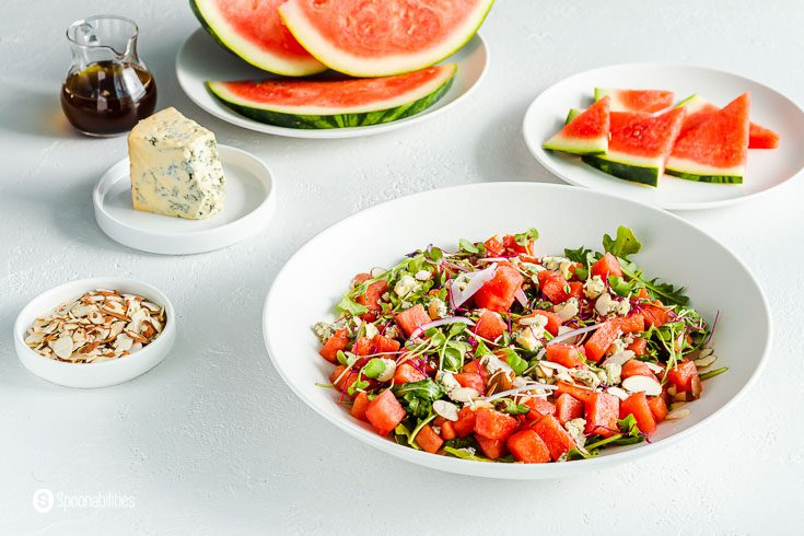 Summer salad in a white serving plate. The salad has watermelon, arugula, blue cheese, almonds, red onions, and dressed with a balsamic vinaigrette. In the background of the photo a small plates with the different ingredients. Recipe at Spoonabilities.com