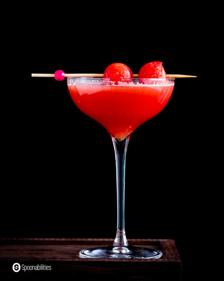 A Close up of this summery and refreshing drink called Watermelon Cosmopolitan. The photo has one tall glass with a drink in a dark background. Recipe at Spoonabilities.com