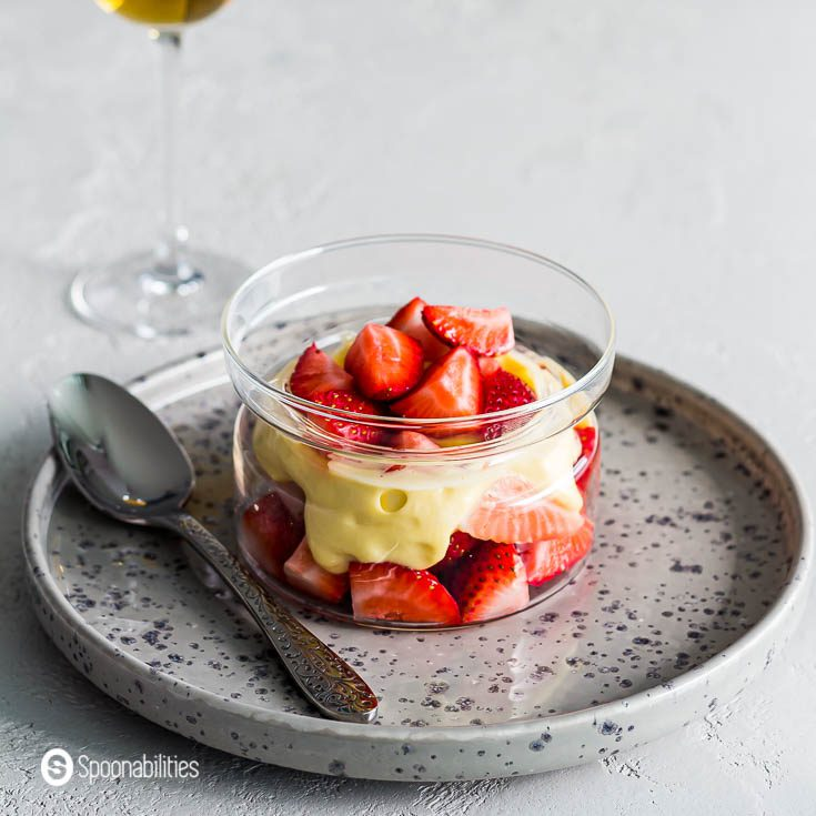 Flat grey plate with a glass bowl with strawberries and Zabaglione. Recipe at Spoonabilities.com
