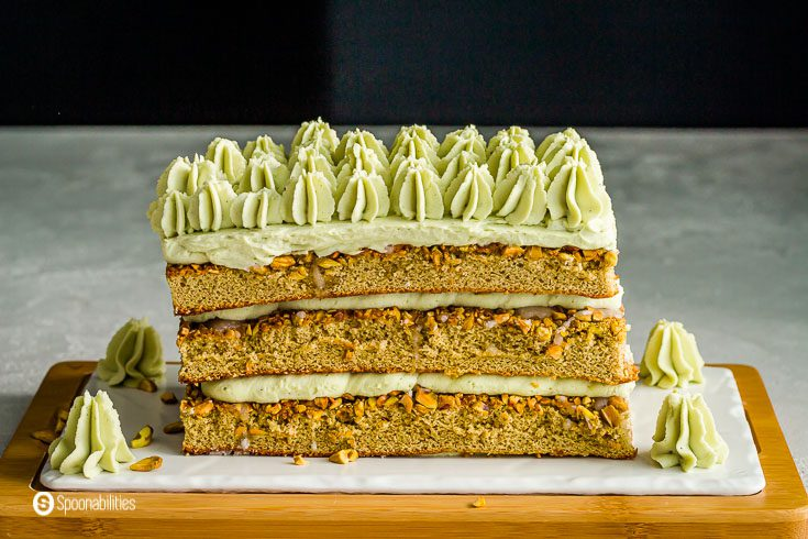 Close of of the whole pistachio tiramisu cake on top of a wooden/porcelain plate. Recipe at Spoonabilities.com