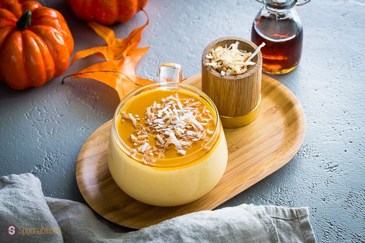 A Glass coffee cup filled with a delicious panna cotta made out of pumpkin, spices, maple syrup, and garnished with toasted coconut flakes. Recipe at Sponabilities.com