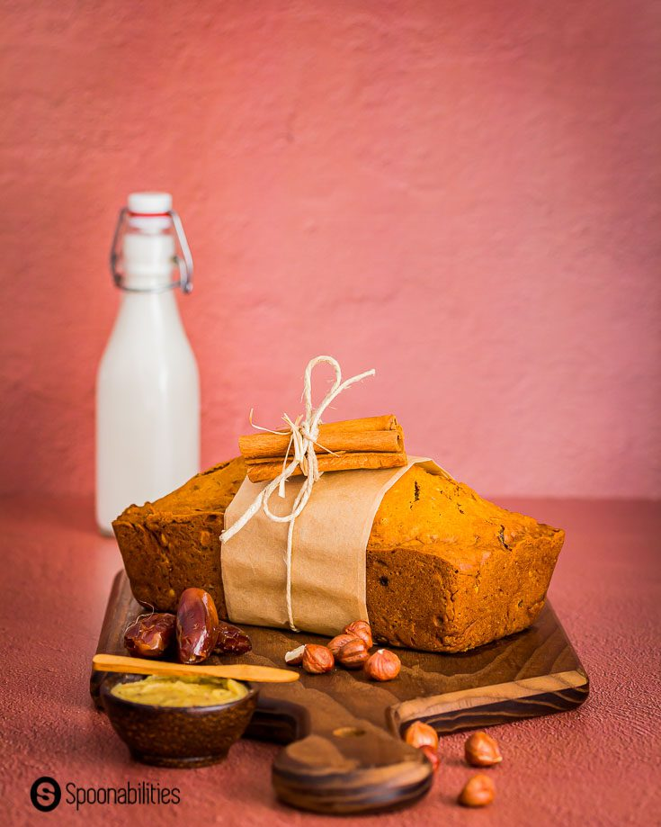 A loaf of bread on top of a wooden board decorated with hazelnuts, dates, and a small dish with brown butter. In the background a bottle with milk. Recipe at Spoonabilities.com