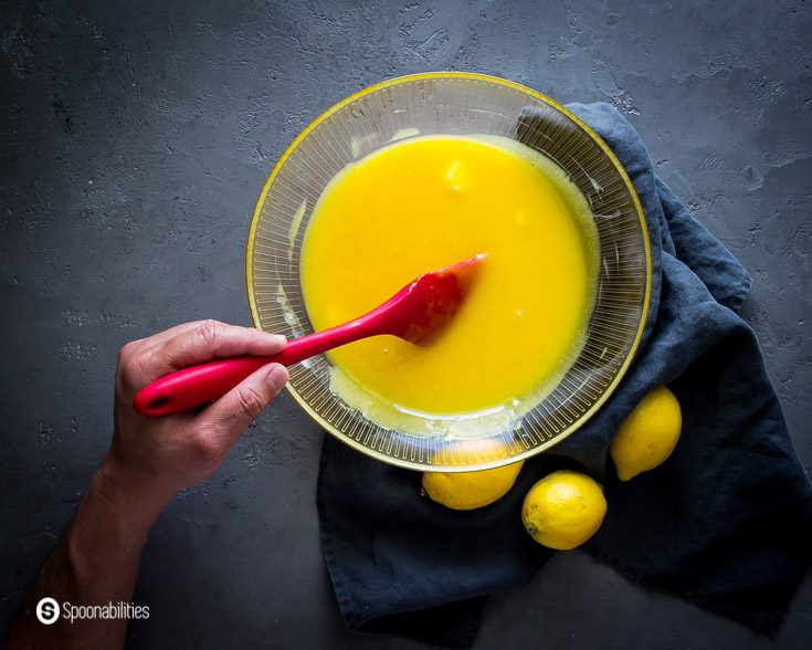Making the lemon curd: A hand with a red spatula stirring the egg custard with the butter. Steps how to make this lemon curd at Spoonabilities.com