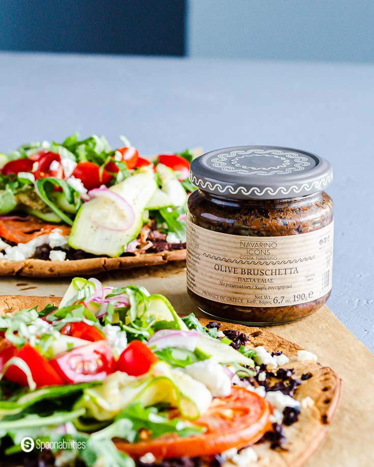 A jar of Olive Bruschetta from Navarino Icons between two veggie pizza. Recipe at Spoonabilities.com