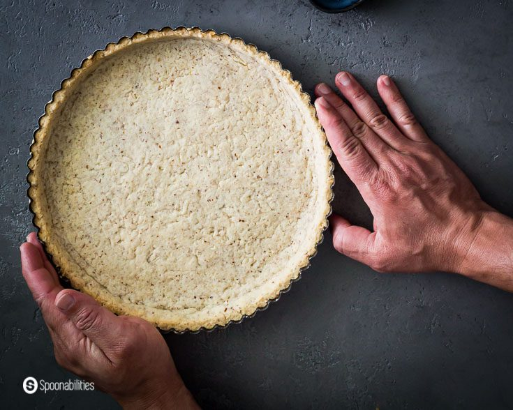 Two hands holding the Par Baked Pie Crust after came out of the oven. Find out in the post what is par baked crust. Recipe at Spoonabilities.com