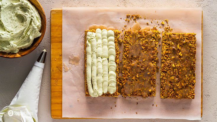 Wooden board and using a piping bag, top the first layer of pistachio tiramisu cake with the whipped mascarpone cream. Recipe at Spoonabilities.com