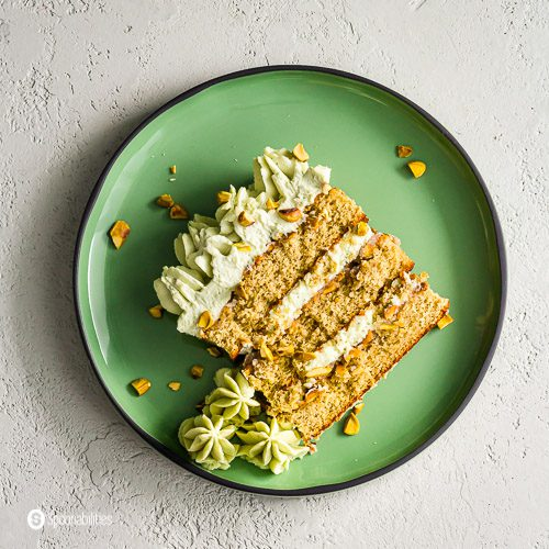 A slice of the pistachio cake on a green plate. This cake is inspired by the Italian traditional dessert Tiramisu and Persian flavors. Recipe at Spoonabilities.com